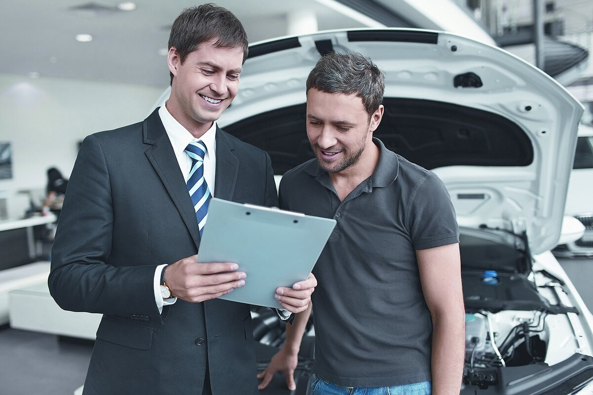 Клиент изучает соглашение при заказе авто в дилерском центре